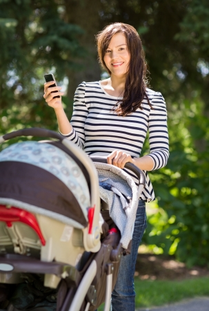 Portrait of beautiful young woman with baby carriage using cell phone in park photo