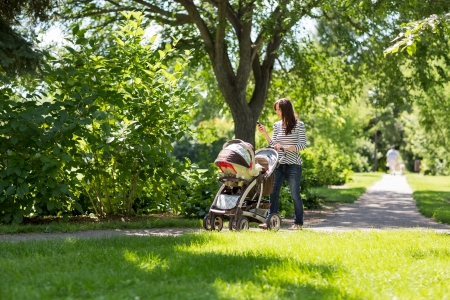 Full length of young mother pushing baby carriage in park photo