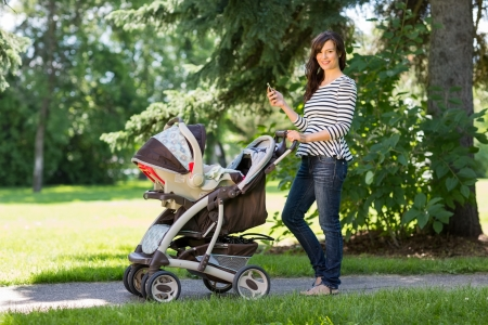 Portrait of happy young mother with cell phone and baby carriage walking in park photo