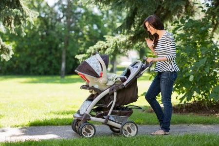 젊은 여자의 전체 길이는 공원에서 유모차를 찾고