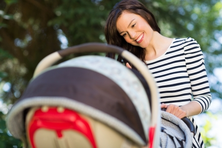 Beautiful young mother looking into baby carriage in park photo