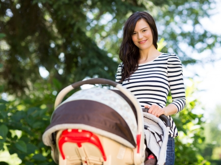 Portrait of beautiful young woman pushing stroller in park photo