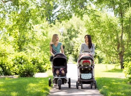 Happy mothers with their baby carriages walking together in park Stock Photo
