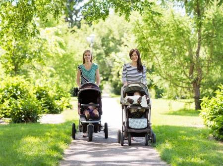 자신의 아기 유모차와 함께 행복 어머니의 초상화 공원에서 함께 산책