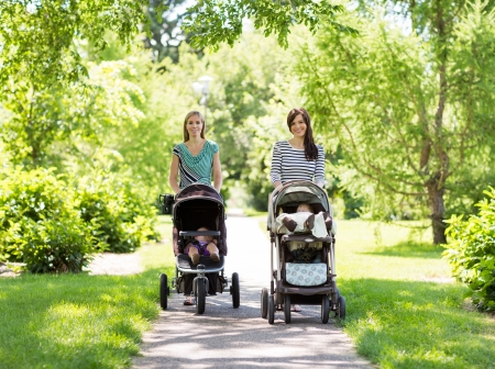 Portrait of happy mothers with their baby strollers walking together in park photo