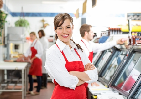 Portrait of confident female butcher standing arms crossed with colleagues  photo