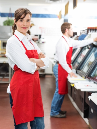 Deli: Portrait of female butcher standing arms crossed with colleague working in background at store