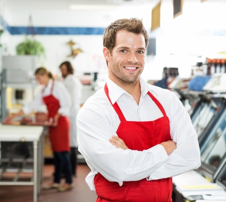 butchers: Portrait of confident male butcher standing arms crossed at store with colleagues working  Stock Photo