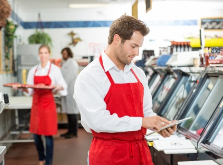 Male butcher using digital tablet at store with colleagues working  photo