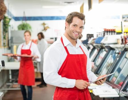 csemege: Portré a boldog hentes, aki digitális tábla a boltban dolgozó kollégák a háttérben Stock fotó