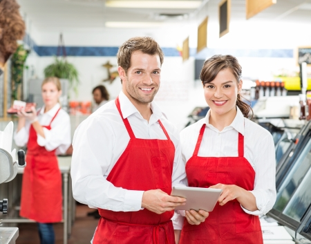 Portrait of happy butchers with digital tablet standing together in store