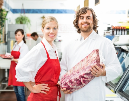 Portrait of confident butchers with meat package standing in store Stok Fotoğraf