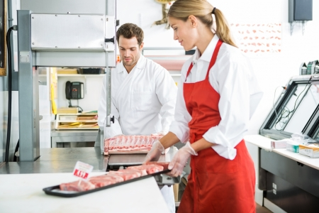 Male and female butchers processing meat in store photo
