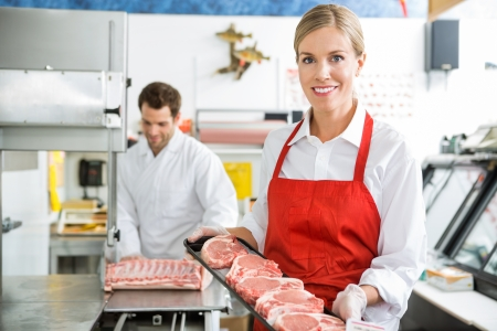 Portrait of beautiful butcher holding meat tray at store with colleague working  photo