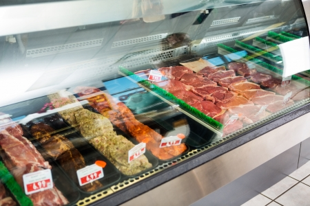 Variety of meat displayed in glass cabinet at butchers shop photo