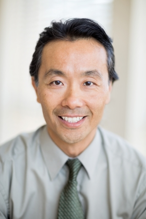 headshot: Portrait of confident Asian male cancer specialist smiling in hospital
