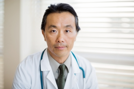 Portrait of confident male doctor with stethoscope around neck at clinic photo