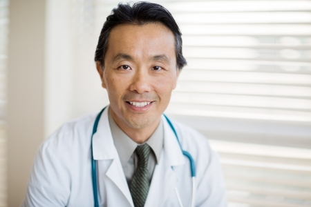 Portrait of Asian male cancer specialist with stethoscope around neck smiling in clinic photo