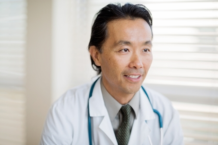 Thoughtful Asian male doctor smiling while looking away in clinic photo