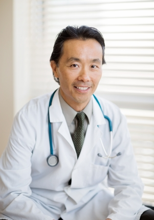 Portrait of Asian male cancer specialist with stethoscope around neck sitting in hospital photo