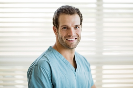 male doctor: Portrait of happy young male nurse in scrubs at clinic