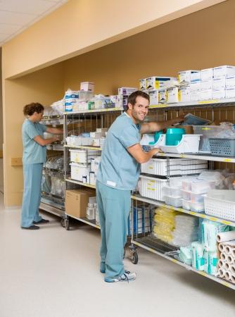 Full length of male and female nurses arranging stock on shelves in hospital storage room photo