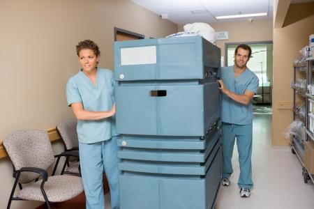 hospitales: Retrato de enfermero empuja la carretilla mientras colega le ayuda en pasillo del hospital Foto de archivo