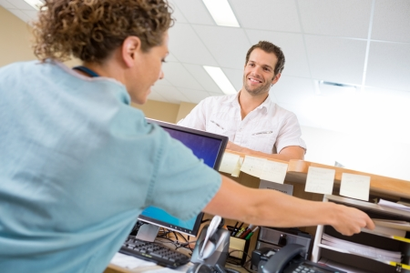 nurses station: Man looking at female nurse working at reception desk in hospital Stock Photo