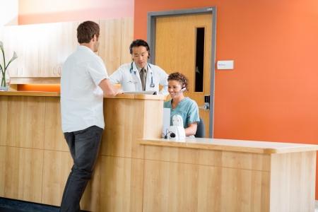 secretarias: Doctor y enfermera que trabaja en el mostrador de recepción mientras paciente de pie en el hospital