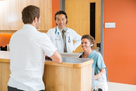 desk area: Medical team with male patient at reception desk in hospital