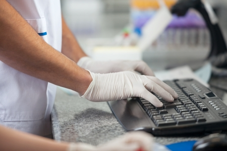cropped image: Cropped image of male technician using computer in medical laboratory Stock Photo
