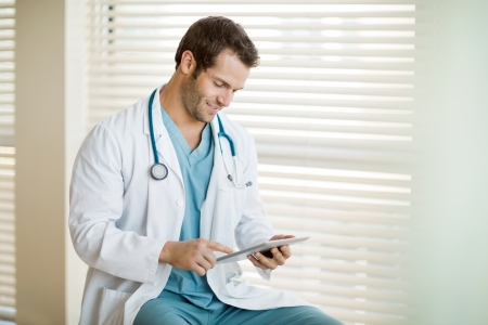 Young male cancer specialist in labcoat using digital tablet at clinic