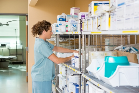 medical supplies: Side view of mid adult female nurse working in storage room of cancer hospital Stock Photo