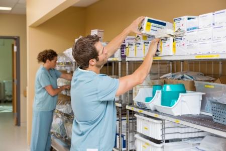 medicines: Nurses arranging stock in hospital storage room