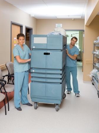 Full length of nurses pushing trolley in hospital hallway photo