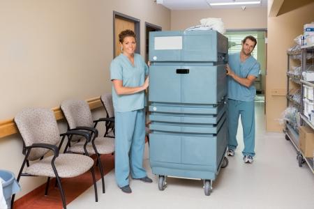 Full length of male and female nurses pushing trolley in hospital hallway photo
