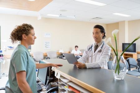 Infirmière et un médecin avec tablette numérique conversation à la réception de l'hôpital Banque d'images