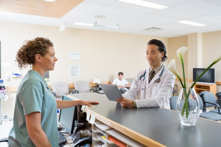 Nurse and doctor with digital tablet conversing at hospital reception photo