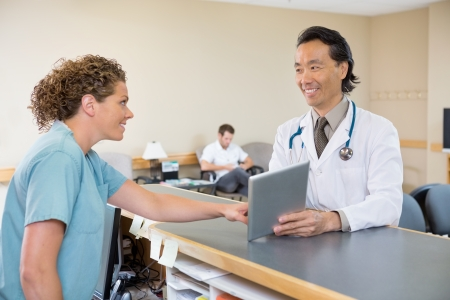 waiting area: Mature doctor and nurse looking at each other while using digital tablet at hospital reception Stock Photo