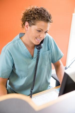 Weibliche Krankenschwester eingehende Telefonate während der Arbeit an der Rezeption im Krankenhaus Standard-Bild