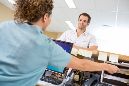 Rear view of nurse assisting man while working at reception desk in hospital photo