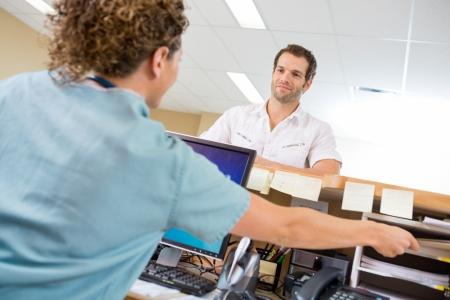 hospitales: Vista posterior de la enfermera ayudando a hombre mientras trabajaba en el mostrador de recepci�n en el hospital