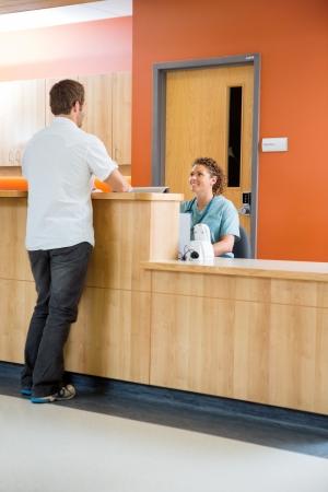 secretarias: Longitud total de paciente masculino de conversar con la enfermera en la recepción en el hospital Foto de archivo