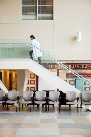 Side view of mature doctor climbing up stairs in hospital photo