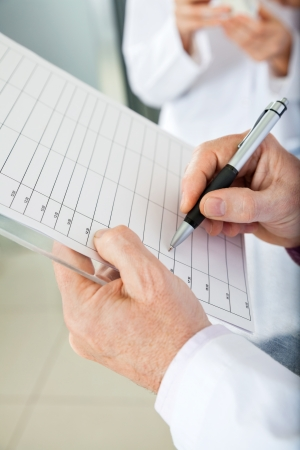 med: Cropped image of researcher writing on clipboard in laboratory