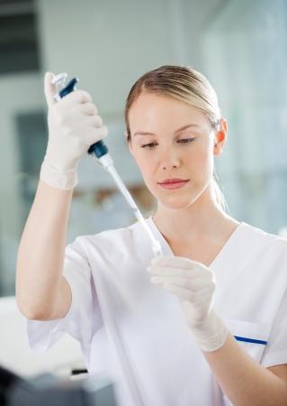 med: Female healthcare worker filling solution into test tube in medical lab