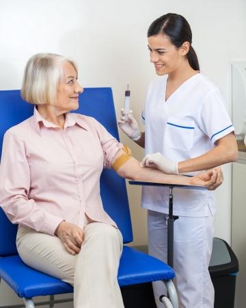 Senior businesswoman undergoing blood test in clinic Stock Photo
