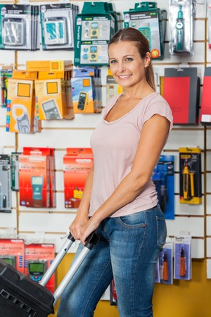 Woman Holding Tool Case In Hardware Store photo