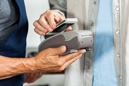 Midsection of salesman accepting payment through NFC technology from customer in hardware store Stock Photo