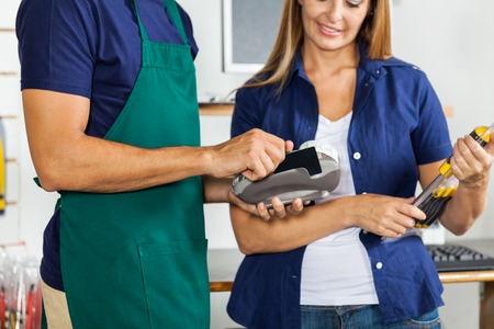 Worker Swiping Credit Card With Woman Holding Screwdriver Set photo